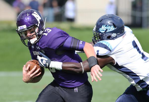 NU QB Trevor Siemian scrambles from the defense of Maine's Axel Ofori Jr. in the first quarter.
