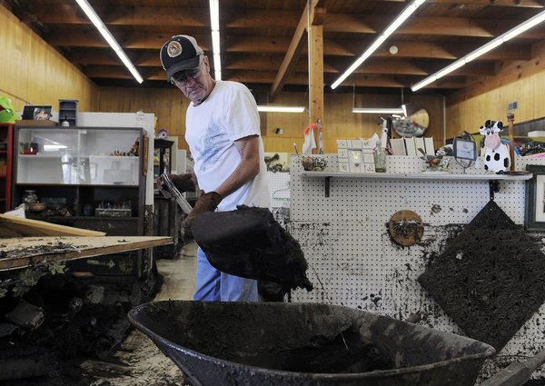 Bob Paetzel scoops mud out of a collectibles store in Loveland, Colo., where floodwaters are receding and rescue and recovery efforts ongoing.
