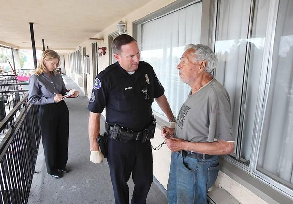 Costa Mesa Police Sgt. Vic Bakkila chats with World War II veteran David Garland about his living conditions at the Sandpiper Motel in Costa Mesa. Bakkila made an effort to connect Garland with veteran services to improve his living situation.