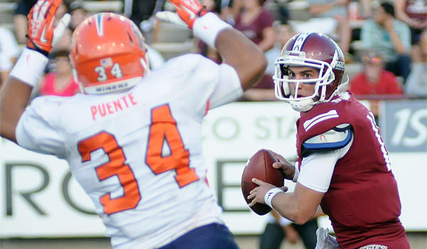 New Mexico State University quarterback Andrew McDonald, right, looks to make a pass over UTEP defender Anthony Puente on Sept. 14.