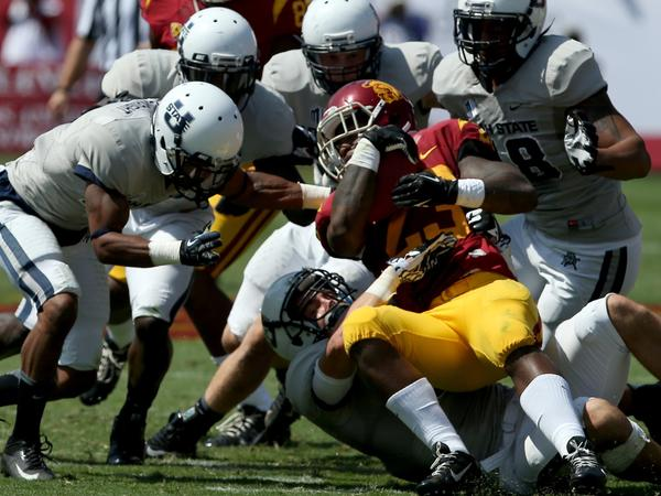 USC trailback Tre Madden is met by a swarm of Utah State defenders in the first quarter Saturday. The Aggies held Madden to 93 yards in 24 carries Saturday, the first time the Trojans running back didn't gain at least 100 yards this season.