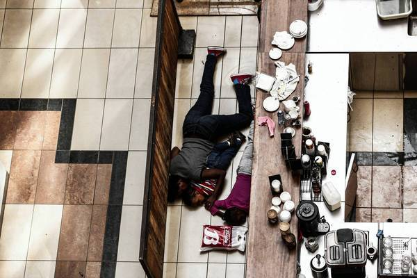 People take cover behind a counter at the Westgate Mall in Nairobi, Kenya, which was attacked by militants.