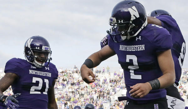 """Northwestern quarterback Kain Colter, shown celebrating a touchdown with running back Stephen Buckley (8) and wide receiver Kyle Prater (21), marked the letters """"APU"""" on his wristbands and towel as part of an organized demonstration."""