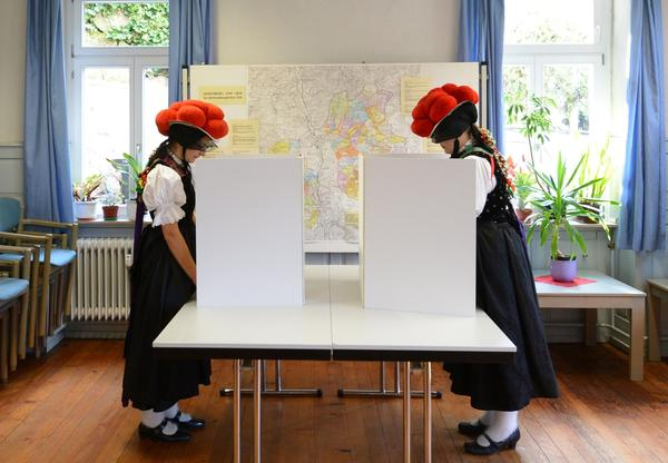 Voters in traditional Black Forest attire cast their ballots Sunday in Hornberg-Reichenbach in southwestern Germany.