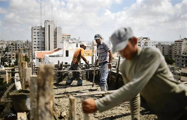 Palestinian workers flatten cement on the roof of a building under construction in Gaza City.
