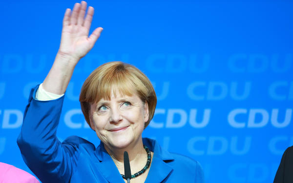 German Chancellor Angela Merkel waves to supporters at the Christian Democratic party's headquarters in Berlin on Sunday. An exit poll indicates that she won a third term as Germany's leader.