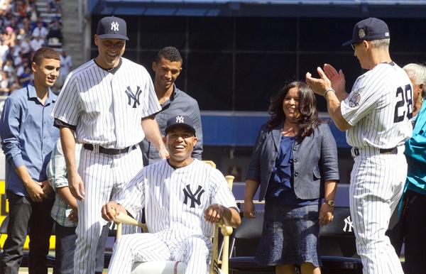 New York Yankees closer Mariano Rivera receives a gift of a rocking chair as shortstop Derek Jeter, left, and manager Joe Girardi (28) and former Yankee Jorge Posada, far left, clap for him during a ceremony before the game at Yankee Stadium.