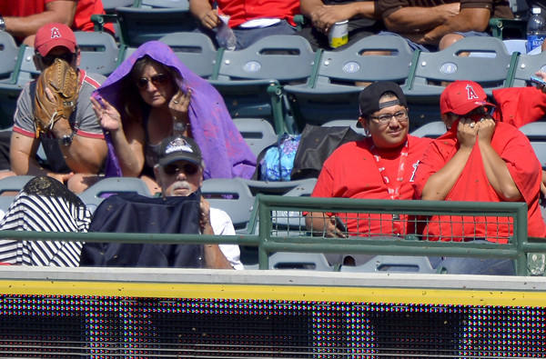 Fans shield themselves from a swarm of bees in the outfield during the Angels-Mariners game on Sunday in Anaheim.