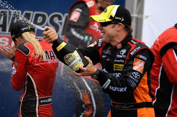 Matt Kenseth, driver of the #20 Home Depot / Husky Toyota, celebrates by spraying champagne in Victory Lane after winning the NASCAR Sprint Cup Series Sylvania 300.