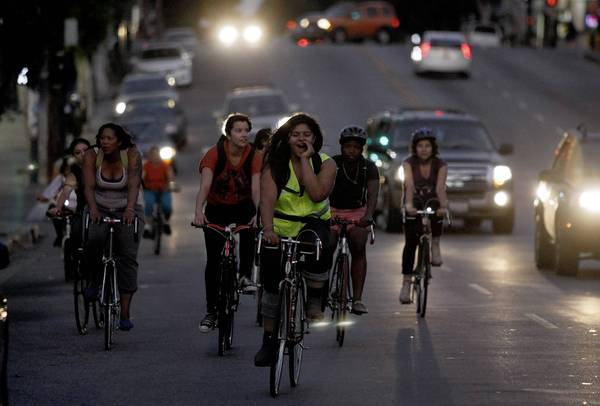 Evelyn Martinez, in the green vest, shouts instructions as she leads other members of the Ovarian Psyco Cycles Brigade on a ride through Boyle Heights. The all-female group is both an answer and a challenge to aggressive male biking culture. Like men's bike crews, it defies L.A.'s monolithic car culture with an in-your-face ethic.