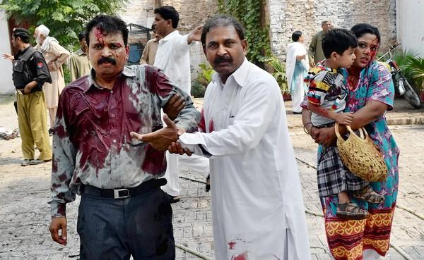 A Pakistani man helps one of the injured after two suicide bombers blew themselves up just after services at a church in Peshawar.