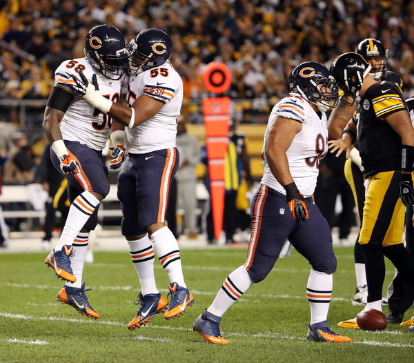 D.J. Williams and Lance Briggs celebrate a sack of Steelers quarterback Ben Roethlisberger in the second quarter.