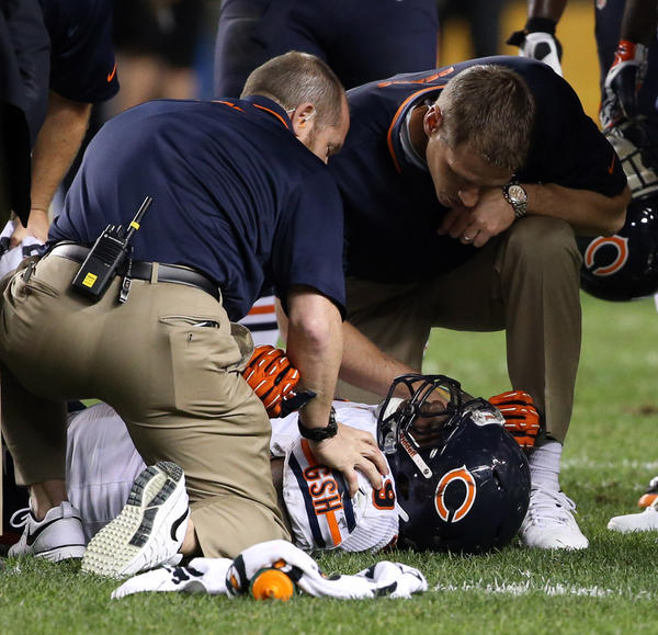 Bears defensive tackle Henry Melton gets medical attention Sunday.