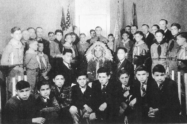 "The first Indian Boy Scout troop in the United States was formed in Petoskey in 1937, under the sponsorship of local businesses that provided uniforms and a place to meet. Chief Joseph Chingwa (center) served as troop leader and is pictured with (left) George Waukazoo and Thomas Adams (right); along with Boy Scouts (front row, from left) Victor Carey, Herman Otto, James Walker, William Dunlop, George Bush, Archie Kiogima, John Duvernay and William ""Smokey"" Chingwa. The scouts in the back came from another troop."