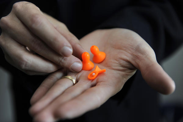 Dan Simon holds a pair of the ABLE (Anti-Blast Ear) plugs. A cross-section of one plug shows a pop-it ball that blocks a shock wave.