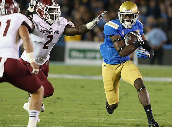 UCLA wide receiver Devin Fuller gets a big gain after catching a pass from quarterback Brett Hundley against New Mexico State at the Rose Bowl on Saturday.