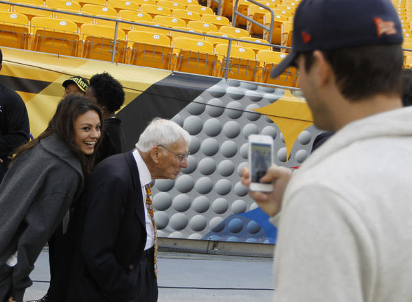 Actress Mila Kunis sneaks next to Pittsburgh Steelers owner Dan Rooney while boyfriend Ashton Kutcher takes a picture Sunday before the Bears-Steelers game at Heinz Field. (Brian Cassella/Chicago Tribune)