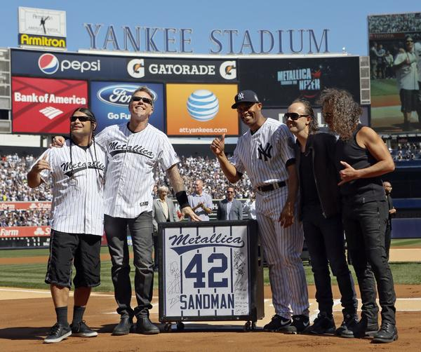 "New York Yankees relief pitcher Mariano Rivera reacts to a gift of a guitar speaker from the band Metallica as the retiring player was honored before their MLB Interleague game with the San Francisco Giants at Yankee Stadium in New York, September 22, 2013. Rivera has always entered the game to the song ""Sandman"" played by the band. Pictured are (L-R): Robert Trujillo, James Hetfield, Mariano Rivera, Lars Ulrich and Kirk Hammett."