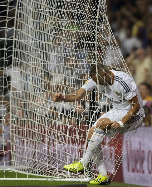 Real Madrid's French forward Karim Benzema reacts in the net during the Spanish league football match Real Madrid CF vs Getafe CF at the Santiago Bernabeu stadium in Madrid on September 22, 2013.