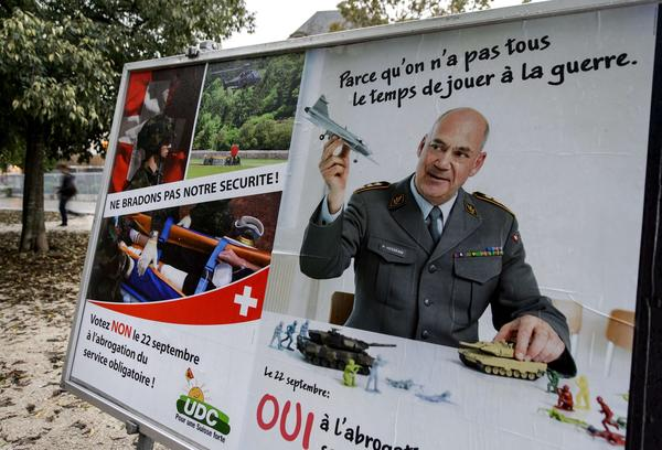 Rival campaign posters stand side by side ahead of Switzerland's vote Sunday that defeated a pacifist group's referendum proposing to end Swiss Army conscription.