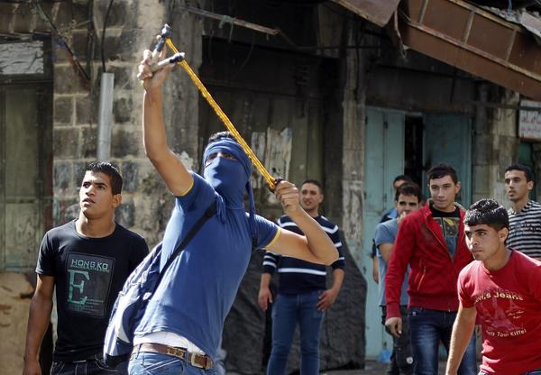 A Palestinian uses a slingshot during clashes with Israeli security forces in the West Bank city of Hebron.