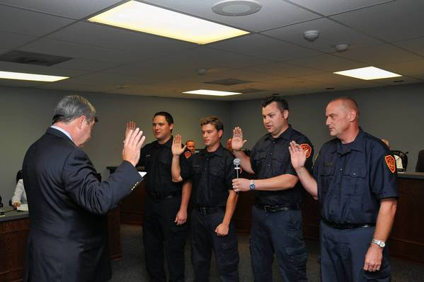 Fire and Police Commissioner John Kelly swears in new firefighter paramedics (from left to right) Jeff Hall, Kevin Michehl, Spencer Cornell and Doug Erb.