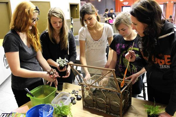 Priscilla Steinmetz, Founder & Executive Director of The Bridge Teen Center, leading a program for students that showed them how to build their own terrariums.