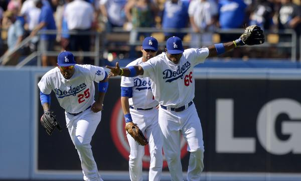 Dodgers outfielders Carl Crawford, left, Andre Ethier, center, and Yasiel Puig celebrate a win over the Tampa Bay Rays in August. The team's surplus of outfielders means someone probably will not be happy with their postseason playing time.