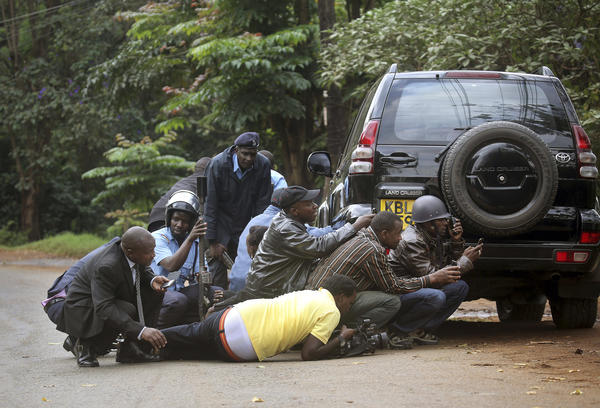 Kenyan security personnel and journalists duck behind a vehicle as heavy gunfire erupts from the Westgate shopping mall in Nairobi.