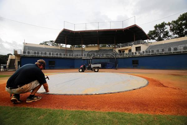 Groundskeeper Jamie Hill covers up home-plate as it begins to rain at the Rollins baseball Harold Alfond Stadium at Harper-Shepherd Field, on Monday, September 23, 2013.