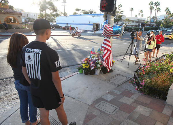 People pause to remember Laguna Beach motor officer Jon Coutchie at a memorial at the intersection of Cleo Street and South Coast Highway, where he collided with a pick-up truck and died at the scene late Saturday night.