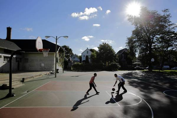 Kevin Herrera, 19, and Miguel Rodriguez, 19, from left, play basketball on the courts at Cornell Square Park, where 13 people were shot last week.