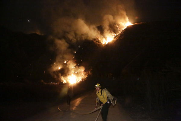 A U.S. Forest Service firefighter pulls on a hose while combating the blaze.