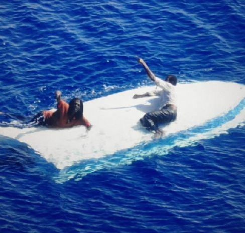 Two men cling to their capsized vessel as a Coast Guard helicopter approaches.