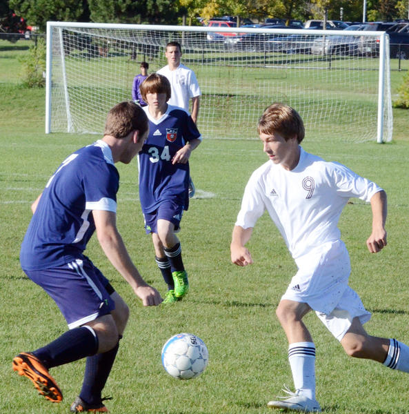 Charlevoix sophomore Walker Drost (right) looks to make a move around Boyne City senior Corey Bohnet during Monday's Lake Michigan Conference match at the Charlevoix High School soccer field. Drost scored a pair of goals as the Rayders defeated the ramblers, 3-0.