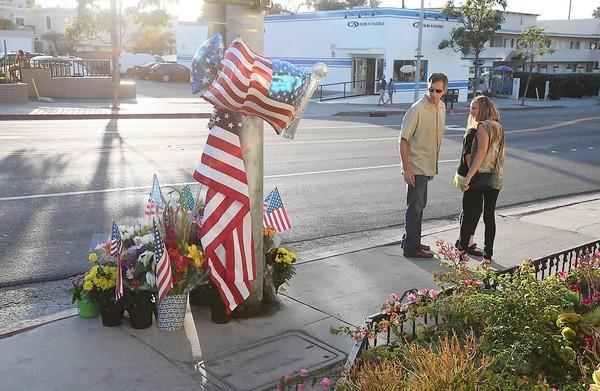 A couple pause to look at a memorial where Laguna Beach Police Officer Jon Coutchie's motorcycle collided with a pick-up at Cleo Street and South Coast Highway. Coutchie died at the scene late Saturday night.