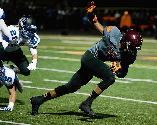 Leon Thornton III 1 of Montini breaks away from two St. Francis tacklers after catching a pass and ran for a first quarter touchdown.