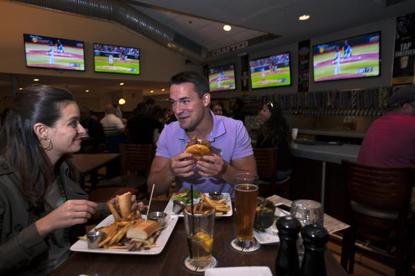 Amy Beales and Lee Demma, both of Baltimore, eat dinner with banks of HD televisions around them at Ale House in Columbia.