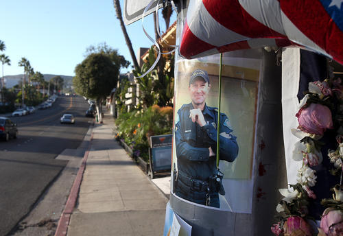 A picture of Laguna Beach police Officer Jon Coutchie posted at the scene where he collided with a pickup truck and died Saturday night at the intersection of Cleo Street and Coast Highway.