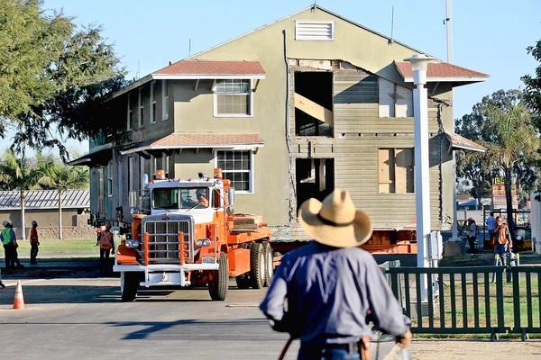 The Memorial Gardens Building is moved from near the Pacific Amphitheatre to Lot G, a temporary location, within the Orange County Fairgrounds on Tuesday morning. The structure is a former Army barracks and is nearly 70 years old.