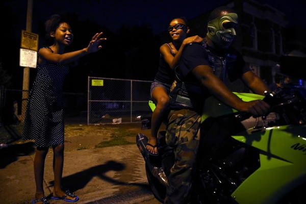 Diamond Foster-Towns waves as her sister Dinah Towns-Wright gets a ride from Gregory Hughes in the 2700 block of W. Polk Street during the weekly motorcycle peace ride led by Ruff Ryders' Dawn Valenti in Chicago.