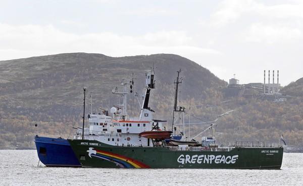 A Greenpeace vessel is escorted by a Russian coast guard boat in Kola Bay.