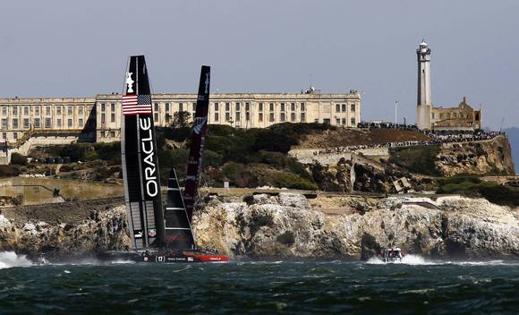 Oracle Team USA (L) and Emirates Team New Zealand sail near Alcatraz Island during Race 8 of the 34th America's Cup yacht sailing race in San Francisco, Calif.