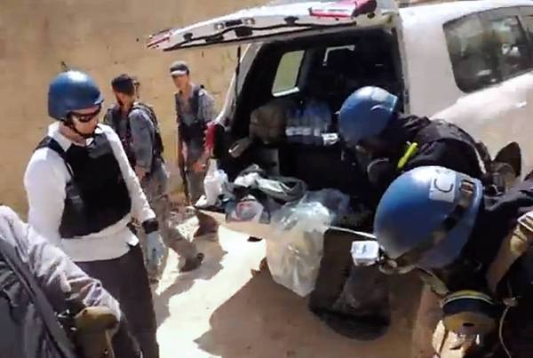 U.N. weapons inspectors reportedly collect samples in Zamalka, east of Damascus, in late August in an image provided by the Local Committee of Arbeen.