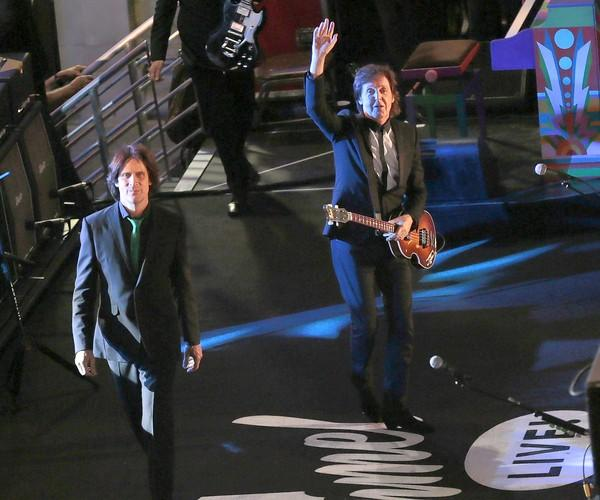 """Paul McCartney, right, and guitarist Rusty Anderson arrive on stage to perform on Hollywood Boulevard.for """"Jimmy Kimmel Live."""""""