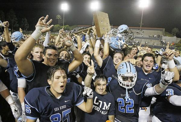 Corona del Mar High players hoist the trophy in a 34-14 victory over Newport Harbor in the Battle of the Bay at Orange Coast College on Friday.
