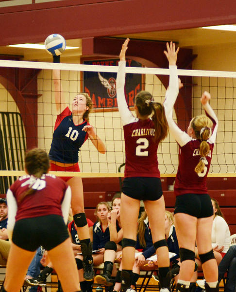 Boyne City senior Kylie Hicks (left) goes around Charlevoix blockers Emily Zabawa (middle) and Gloria Greene (right) during a Lake Michigan Conference match Tuesday. The Ramblers defeated the Rayders in three sets to remain unbeaten in the Lake Michigan Conference.