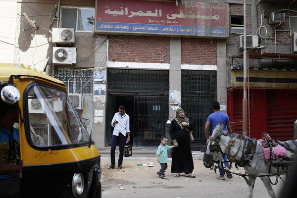 Egyptians walk in front of Al-Omraniyah hospital, run by the Muslim Brotherhood's Islamic Medical Assn., in Cairo on Saturday. An Egyptian court this week ordered a ban of the Brotherhood and confiscation of its assets, followed Wednesday by an order closing a newspaper linked to the group.
