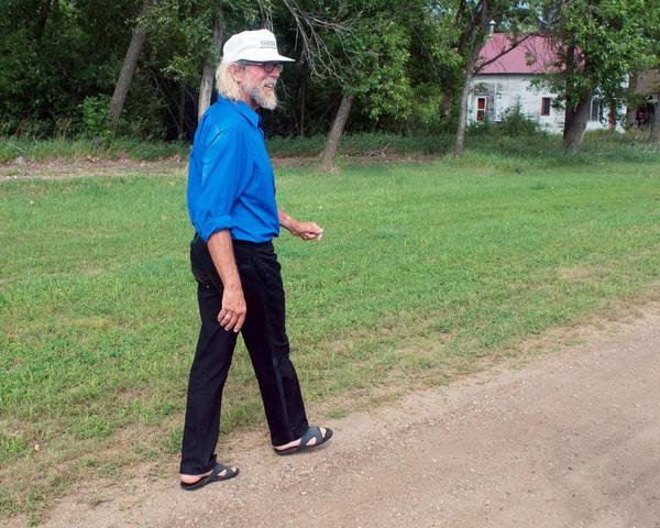 White supremacist Craig Cobb walks along Main Street toward his home in Leith, N.D., last month. Cobb, 61, has purchased more than a dozen lots in Leith and over the last year he has invited fellow supremacists to move there and help him to transform the town of 16 people into a white enclave.
