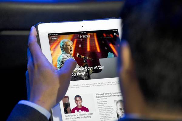 An E3 attendee reads a Los Angeles Times newspaper article using the Flipboard app on an iPad as he waits for the start of the Nintendo E3 2012 media briefing in Los Angeles on June 5, 2012.